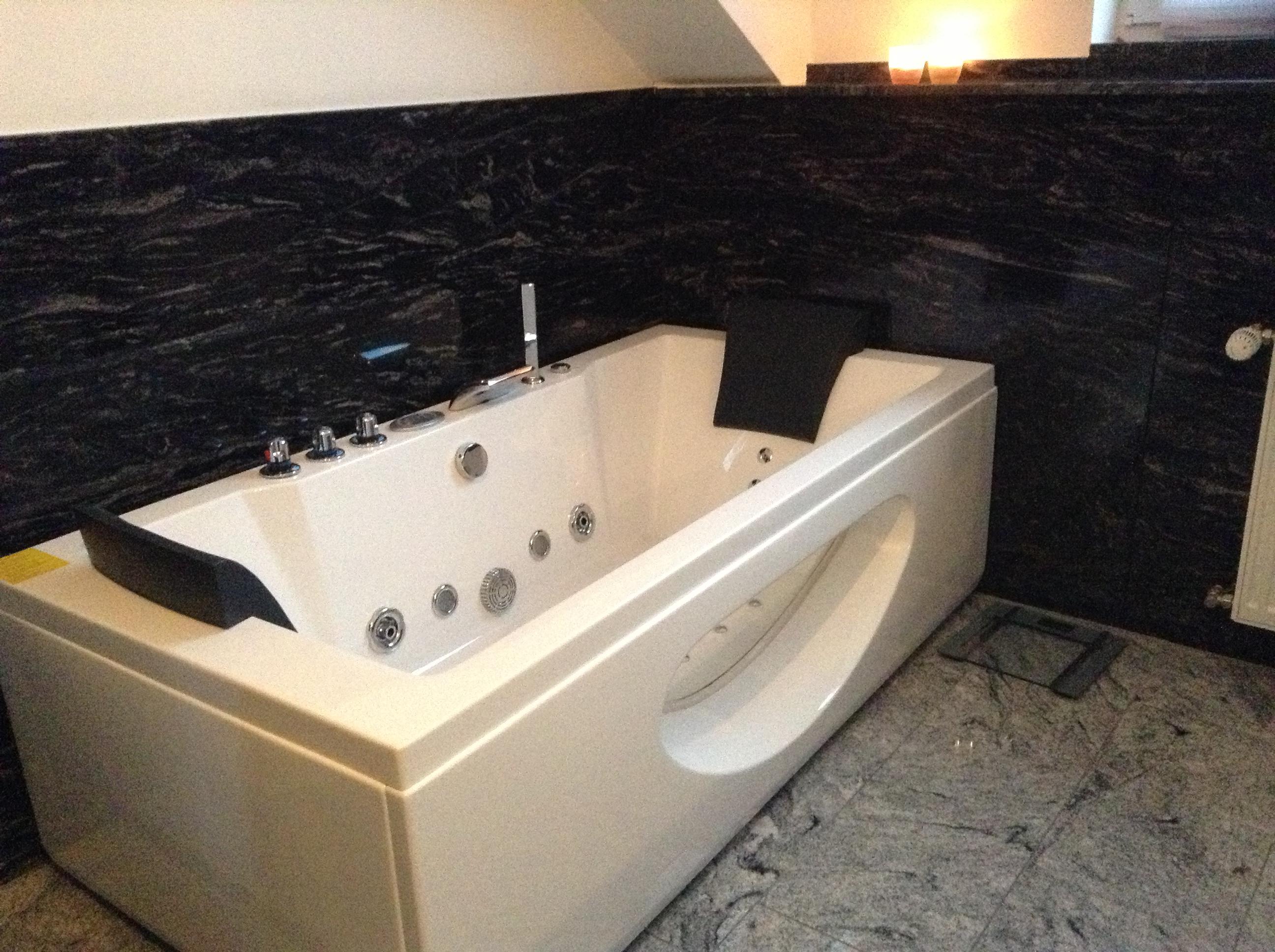 Badewanne und schwarzer Granit im Bad